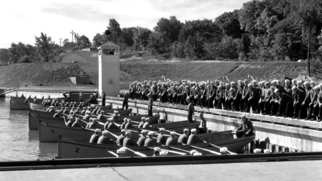 u.s. naval recruits grip oars as they prepare to row lifeboats out into a basin. - military recruit stock videos & royalty-free footage