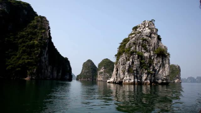 navigation in der nähe riesiger felsspaltung an der berühmten halong bay in vietnam - dschunke stock-videos und b-roll-filmmaterial