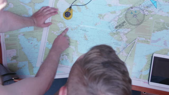 navigation of map charts on a sailboat navigating seas and oceans. - barca da diporto video stock e b–roll
