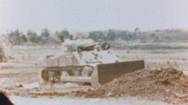 s navy and marine ground forces driving lvt vehicle across open field and tank dozer operator clearing debris and path through jungle during wwii... - landungsboot stock-videos und b-roll-filmmaterial