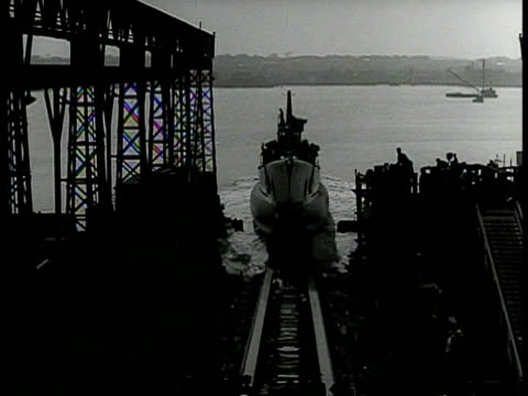 Navy battleship being launched in harbor HA WS Submarine down ramp from shipyard into water WS Submarine launching into harbor WWII