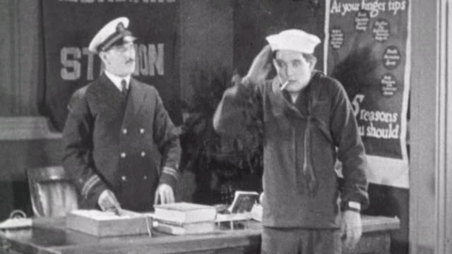 vídeos de stock, filmes e b-roll de navy blues silent short / man crashes into naval recruitment poster / man enlists / officer demands that he stop smoking / man runs to report to uss... - 1923