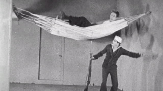 vídeos de stock, filmes e b-roll de navy blues silent short / naval recruit cuts up the hammocks / naval recruit breaks the bunks and makes everyone angry / bunk problems on september... - 1923