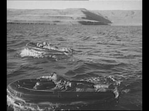 stockvideo's en b-roll-footage met navy boat moves on water / montage frogmen lie on motorized rafts move across water / 1950 british crew stands on deck of small cabin cruiser /... - zwemvlies