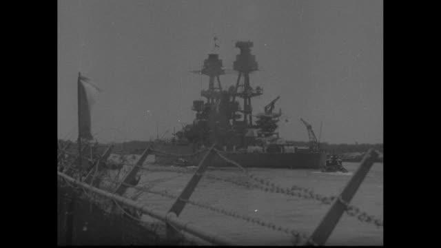 vidéos et rushes de a navy captain of ship holding a megaphone on ship bridge / a railing with a tattered white flag and battleship cruising beyond / flying b17s seen... - vaisseau de guerre