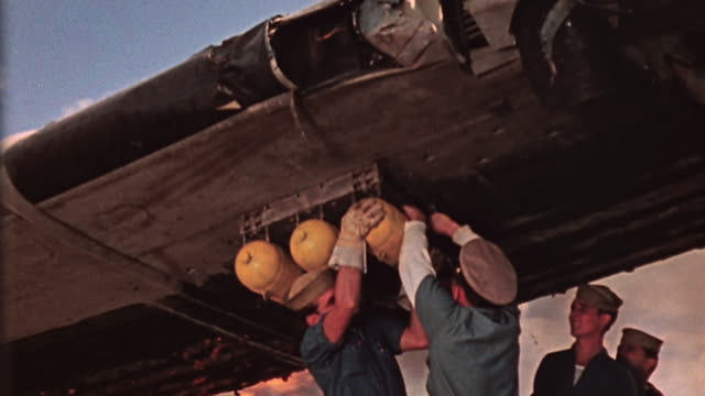 s navy crewmen hastily removing bombs from underside of damaged burning aircraft wing at bombed hangar during attack on pearl harbor / hawaii united... - 真珠湾攻撃点の映像素材/bロール