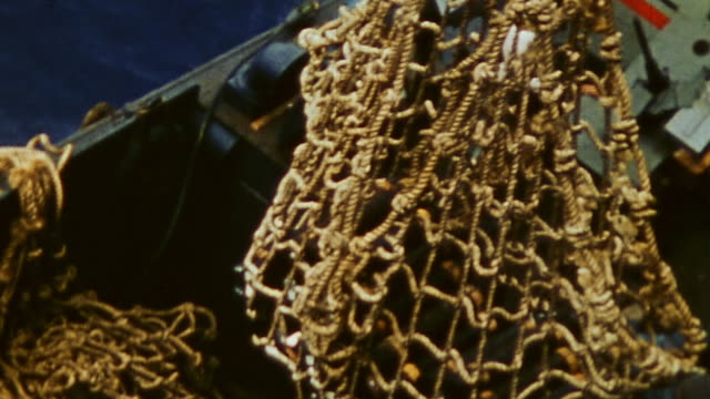 navy crewmen maneuvering cargo nets loaded with 105mm shells from ship to landing craft nesting alongside during wwii / peleliu, palau - ammunition stock videos & royalty-free footage