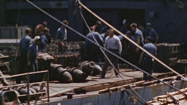 vidéos et rushes de navy crewmen transferring large general purpose bombs via winch and cargo net from ammunition ship to aircraft carrier while underway / okinawa, japan - vaisseau de guerre