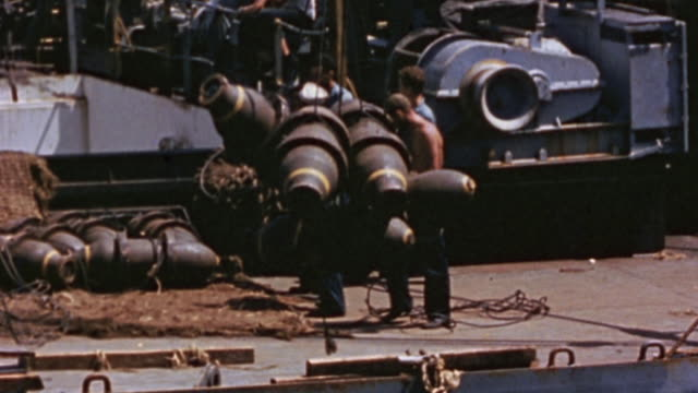 vidéos et rushes de s navy crewmen transferring large general purpose bombs via winch and cargo net from ammunition ship to aircraft carrier while underway / okinawa... - vaisseau de guerre
