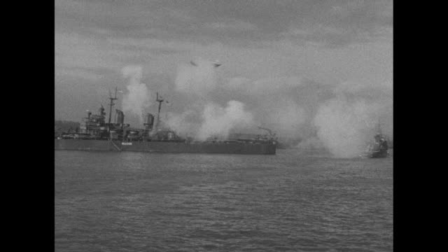 Navy cruiser USS Macon floating down Hudson River firing guns / shot from moving ship of ships at anchor at piers along river / two shots of US Navy...