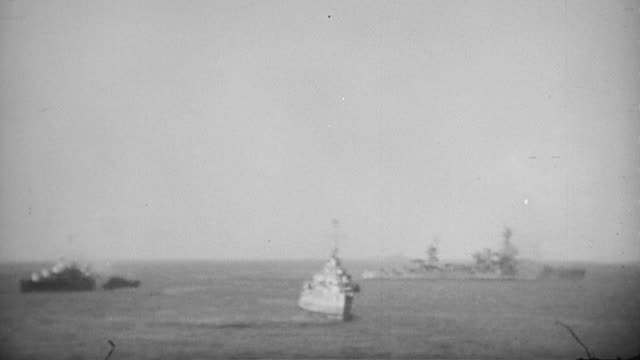 s navy destroyer and battleship firing off the coast of iwo jima and smoking rising over island during world war ii / japan - iwo jima island stock videos & royalty-free footage
