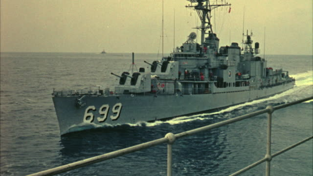 1967 MS Navy destroyer moving past another military ship