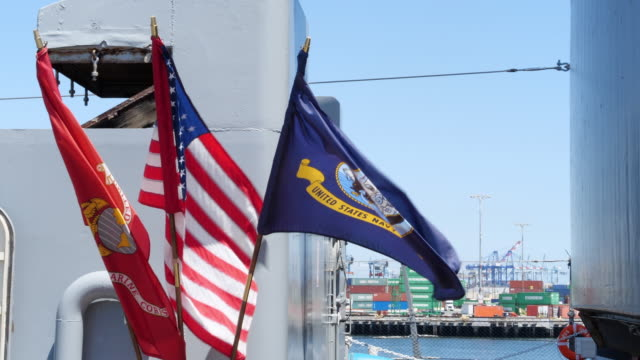 stockvideo's en b-roll-footage met us navy flag flying with port activities in the background in lone beach california - amerikaanse zeemacht