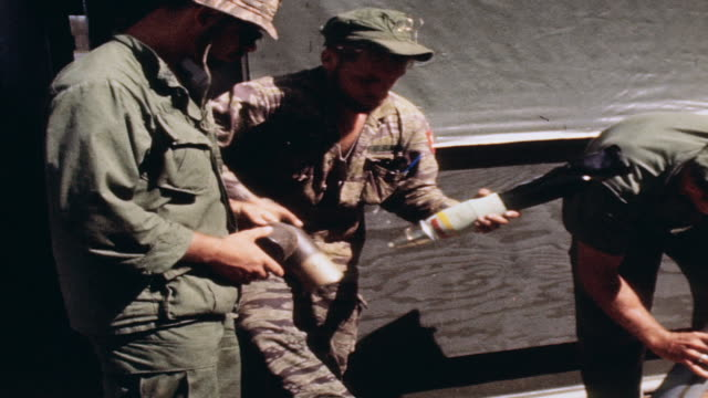 stockvideo's en b-roll-footage met s navy gunners unpacking rockets from canisters assembling them and setting the timing aboard mobile base in river / vietnam - amerikaanse zeemacht