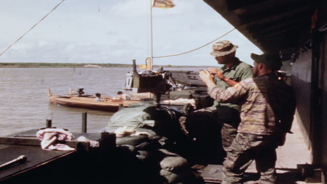 S Navy gunners working on 50 caliber machine gun on mobile gun platform in river / Vietnam