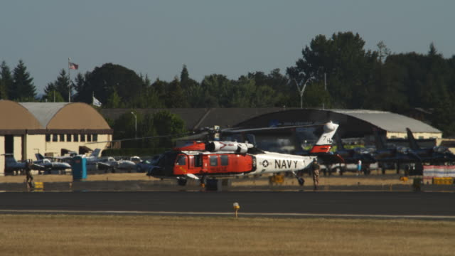 Navy helicopter idling on tarmac behind heat waves