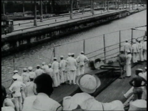 navy men on deck of battleship going through panama canal some looking though binoculars as another boat is approaching / republic of panama - anno 1906 video stock e b–roll