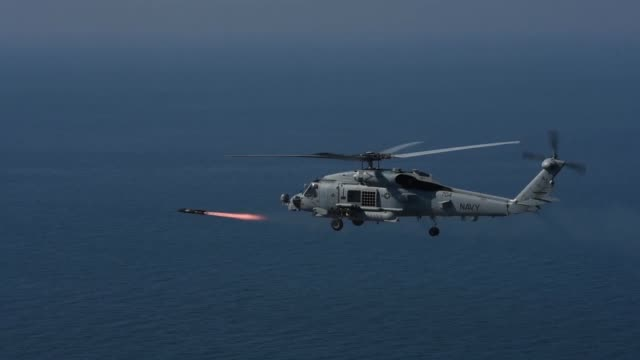 navy mh-60r seahawk helicopter assigned to the 'spartans' of helicopter maritime strike squadron shoots an agm-114n hellfire missile during exercise... - nato stock-videos und b-roll-filmmaterial