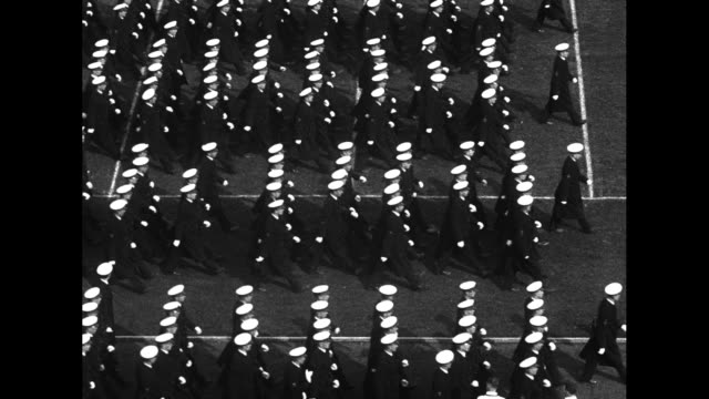 """vidéos et rushes de navy midshipmen parade in formation on football field before game / intertitle: """"navy kicks off"""" elevation shot of sailors in stands with hats on and... - pom pom girl"""
