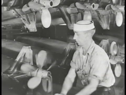 vidéos et rushes de navy officer standing w/ hands over propped torpedo w/ turning propellers sailor in arsenal loading artillery shells onto cart xws us navy vessel w/... - marin