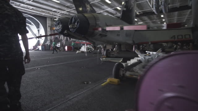 us navy officer walks through plane hangar and fighter jets, tracking shot - 飛行機格納庫点の映像素材/bロール