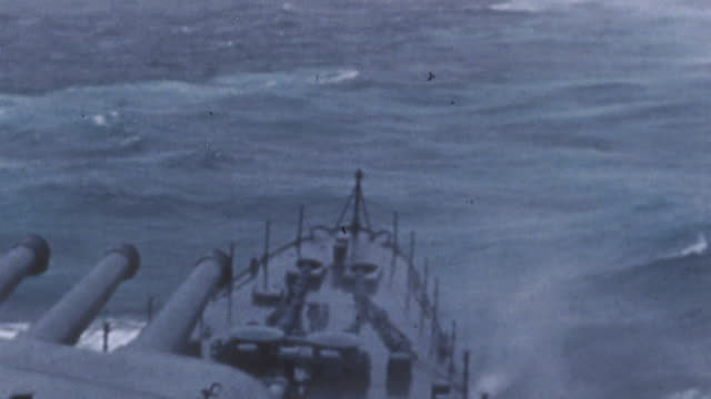 s navy pacific fleet underway in heavy seas with bow waves breaking over the bow of uss salt lake city and eightinch naval guns aimed forward during... - militärschiff stock-videos und b-roll-filmmaterial