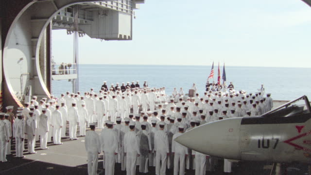 navy personnel in white uniforms stand on the deck of an aircraft carrier during a funeral. - funeral stock videos & royalty-free footage