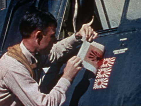 Navy pilot painting ensign of Imperial Japanese Navy on plane to represent third 'kill'