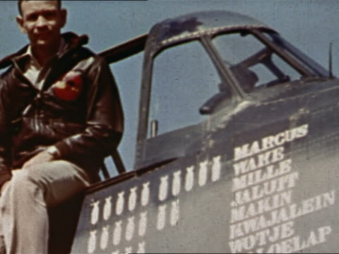 Navy pilot posing next to plane with names of Pacific air strikes painted on cockpit