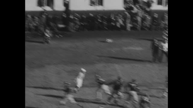 navy player harold hamburg fumbles but recovers ball / hamburg runs with ball and is tackled / navy team makes pass but player is tackled / navy... - アメフト ファーストダウン点の映像素材/bロール