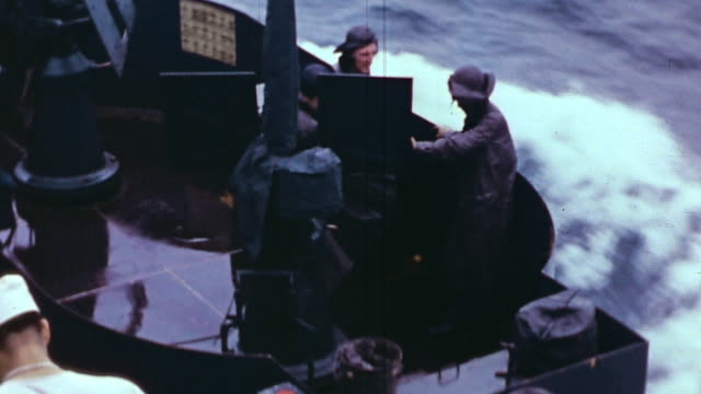 navy sailor looking through binoculars in bird's nest on cruiser, foaming, stormy water, sailors washing decks, gun turrets aimed and ready for fire... - schiffsdeck stock-videos und b-roll-filmmaterial