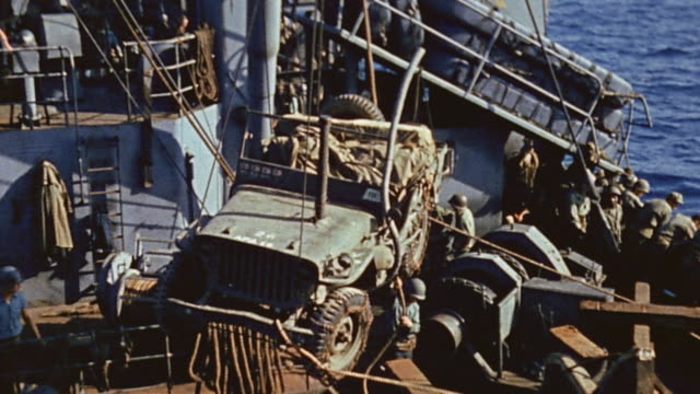 s navy sailors with crane lifting jeep and trailer from cargo ship to landing craft alongside / okinawa japan - 四輪駆動車点の映像素材/bロール