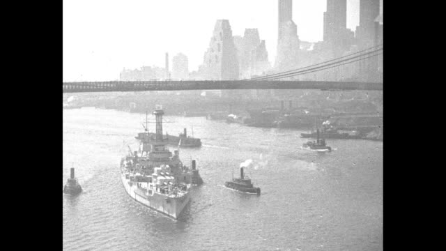 vídeos de stock, filmes e b-roll de navy ship accompanied by tugboats sails past manhattan passes underneath bridge / tiltdown ms the battleship / cu the ship's tower passes by / headon... - manhattan bridge