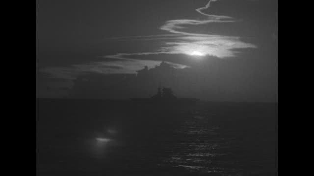 navy ships and clouds silhouetted against setting sun / ms crew man guns on us aircraft carrier / mls plane lands on carrier in choppy seas / pan... - pacific war stock videos and b-roll footage
