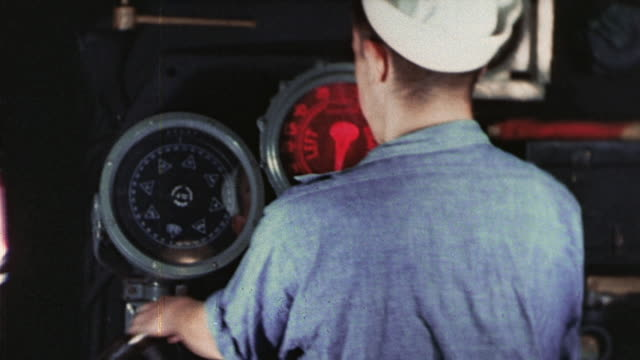 S Navy submarine crewman manning controls and watching depth gauge and officer looking through periscope during WWII