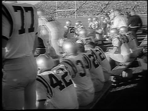 vídeos de stock, filmes e b-roll de navy team on benches at army vs. navy football game / philadelphia / newsreel - liga esportiva