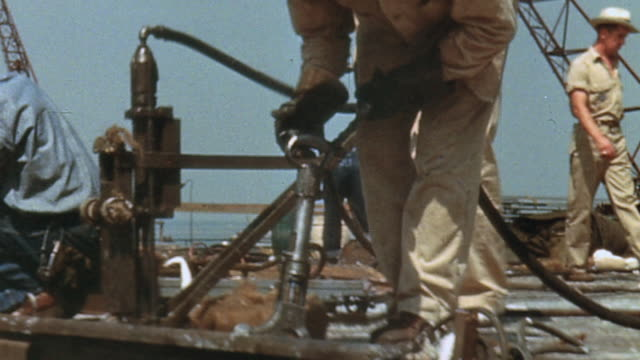 Navy yard workers hammering and drilling on the flight deck of the USS Yorktown under construction / Newport News Virginia United States