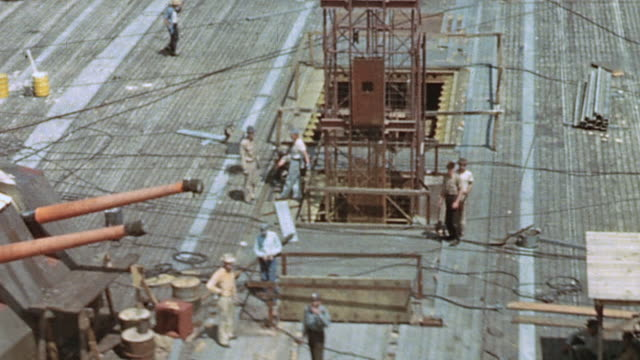 Navy yard workers installing 5inch guns and deck plates on USS Yorktown under construction / Newport News Virginia United States