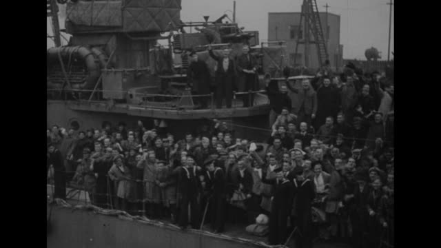 Nazi banners lying on ground / British ship 'Cossack' streaming into harbor at Leith / VS freed British prisoners on deck of ship / three shots of...