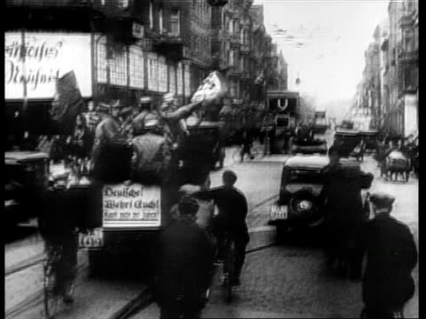 stockvideo's en b-roll-footage met nazi brownshirts on trucks driving thru streets / crowd walking on street past jewish shops / anti-semitism. opening of the official anti-semitic... - 1933