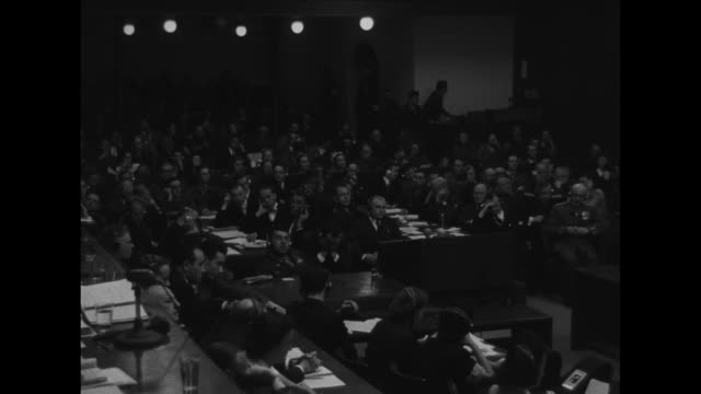 nazi defendants in dock during nuremberg trials military police guards stationed behind them crowded courtroom judges panel / cu judge reading... - 言語翻訳点の映像素材/bロール