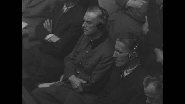 nazi defendants sitting in prisoner's dock listening from left to right wilhelm keitel ernst kaltenbrunner and hans frank / overhead shot of british... - processi di norimberga video stock e b–roll