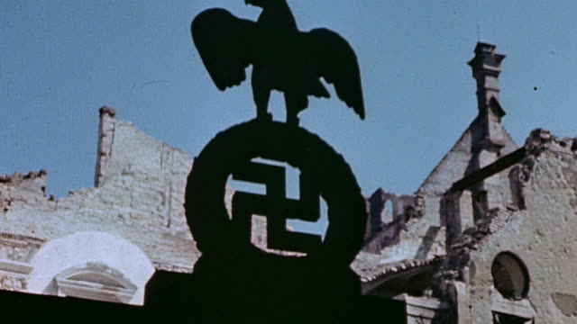 la nazi eagle and swastika against the sky and bomb damaged buildings / munich germany - 1945 stock-videos und b-roll-filmmaterial