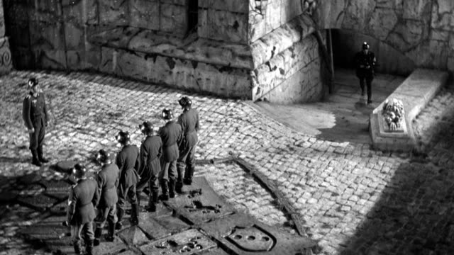 vídeos de stock, filmes e b-roll de a nazi firing squad waits as prisoners are led into a fortress courtyard. - oficial posto militar