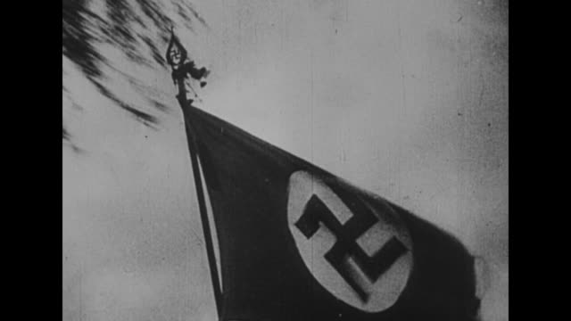vídeos de stock e filmes b-roll de nazi flag flutters in breeze as it moves atop an unseen vehicle / drive-by shot brown shirts march in a town / brown shirt, facing camera, moves away... - nazismo