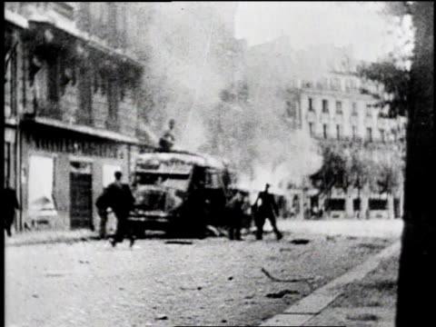 nazi flag hanging from building / men with guns running in the streets / truck driving through smoke / men firing guns / citizens putting out their... - civilperson bildbanksvideor och videomaterial från bakom kulisserna
