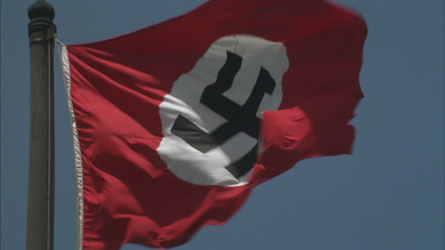 a nazi flag with red background, white circle, and black swastika flies in the wind against a blue sky. - ナチズム点の映像素材/bロール