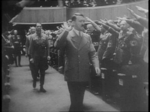 nazi leader rudolf hess walks past nazi soldiers in uniform swastika flags salutes / hess in nazi uniform shaking hands with german soldiers officers... - anno 1941 video stock e b–roll