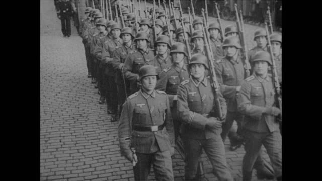 Nazi officers and peasant crowd watch as new Estonian Hitler Youth parade downtown