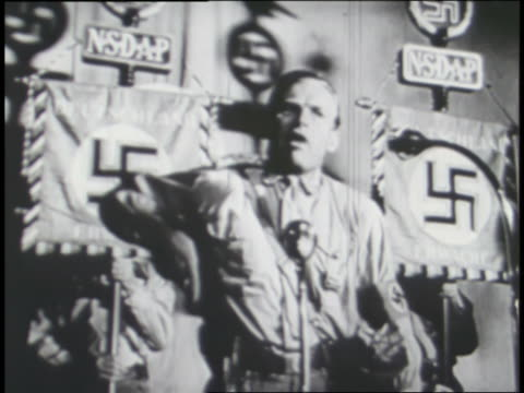 a nazi official speaks to an excited crowd; a hand holds a billy club and shoots a gun. - 緊急用具点の映像素材/bロール